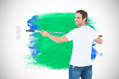 Composite image of happy man using paint roller Stock Photography