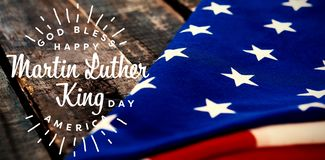 Composite image of happy martin luther king day, god bless america. Happy Martin Luther King day, god bless america against folded american flag on wooden table stock illustration
