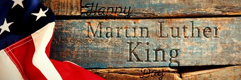 Composite image of happy martin luther king day. Happy Martin Luther King day against american flag on old wooden table stock image