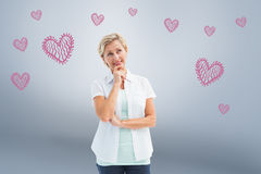 Composite image of happy mature blonde thinking with hand on chin Stock Image