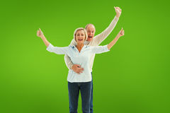 Composite image of happy mature couple cheering at camera Stock Image
