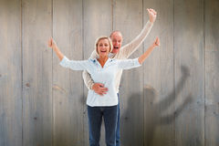 Composite image of happy mature couple cheering at camera Stock Photography