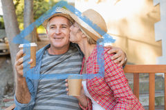 Composite image of happy mature couple drinking coffee on a bench in the city Royalty Free Stock Images