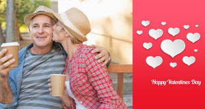 Composite image of happy mature couple drinking coffee on a bench in the city Royalty Free Stock Image