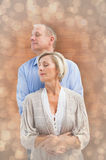 Composite image of happy mature couple embracing with eyes closed Stock Image