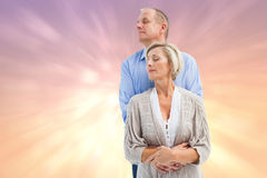 Composite image of happy mature couple embracing with eyes closed Stock Photography