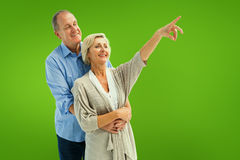 Composite image of happy mature couple embracing and looking Royalty Free Stock Photos