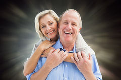 Composite image of happy mature couple embracing smiling at camera Royalty Free Stock Photos