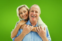 Composite image of happy mature couple embracing smiling at camera Stock Images