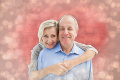 Composite image of happy mature couple embracing smiling at camera Stock Image