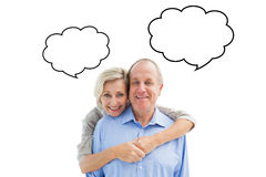 Composite image of happy mature couple embracing smiling at camera Stock Photography