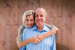 Composite image of happy mature couple embracing smiling at camera Royalty Free Stock Image
