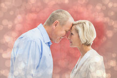 Composite image of happy mature couple facing each other Royalty Free Stock Photo
