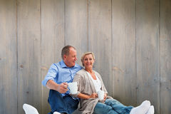 Composite image of happy mature couple having coffee Stock Photo
