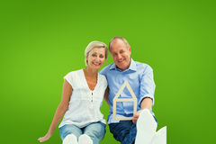 Composite image of happy mature couple holding a house shape. Happy mature couple holding a house shape against green vignette Stock Photo