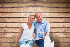 Composite image of happy mature couple holding a house shape. Happy mature couple holding a house shape against wooden planks background Stock Photos