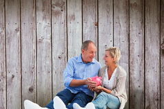 Composite image of happy mature couple holding piggy bank Royalty Free Stock Photo