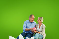 Composite image of happy mature couple holding piggy bank Royalty Free Stock Images