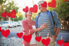 Composite image of happy mature couple hugging in the city. Happy mature couple hugging in the city against hearts hanging on a line Stock Photos