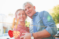 Composite image of happy mature couple hugging in the city Royalty Free Stock Photos