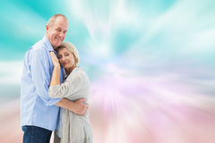 Composite image of happy mature couple hugging and smiling Stock Images