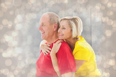 Composite image of happy mature couple hugging and smiling Stock Photos
