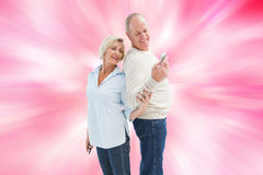 Composite image of happy mature couple looking at smartphone together Royalty Free Stock Photography