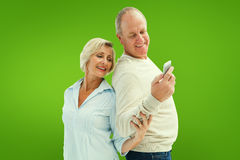Composite image of happy mature couple looking at smartphone together Royalty Free Stock Images
