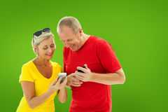 Composite image of happy mature couple looking at smartphone together Stock Image