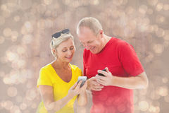 Composite image of happy mature couple looking at smartphone together Stock Images