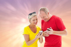Composite image of happy mature couple looking at smartphone together Stock Photography