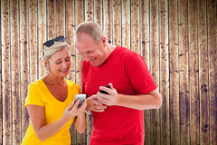 Composite image of happy mature couple looking at smartphone together Royalty Free Stock Photos