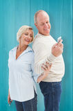 Composite image of happy mature couple looking at smartphone together Royalty Free Stock Photo