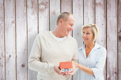 Composite image of happy mature couple with model house. Happy mature couple with model house against wooden planks Royalty Free Stock Image