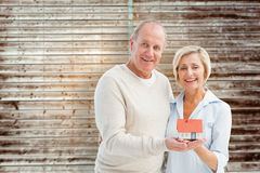 Composite image of happy mature couple with model house. Happy mature couple with model house against wooden planks Royalty Free Stock Photos