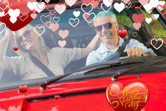 Composite image of happy mature couple in red cabriolet Royalty Free Stock Images