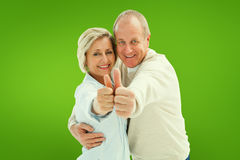 Composite image of happy mature couple showing thumbs up Royalty Free Stock Photography