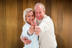 Composite image of happy mature couple showing thumbs up Royalty Free Stock Photo