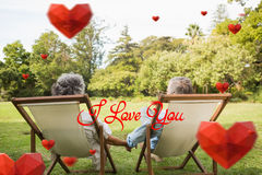 Composite image of happy mature couple sitting in park Stock Photography
