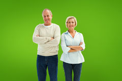 Composite image of happy mature couple smiling at camera. Happy mature couple smiling at camera against green vignette Royalty Free Stock Images