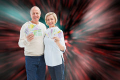 Composite image of happy mature couple smiling at camera showing money. Happy mature couple smiling at camera showing money against digitally generated twinkling stock photo