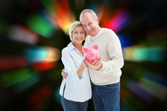 Composite image of happy mature couple smiling at camera showing piggy bank Stock Photography