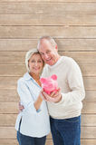 Composite image of happy mature couple smiling at camera showing piggy bank Royalty Free Stock Photo