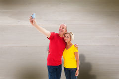 Composite image of happy mature couple taking a selfie together. Happy mature couple taking a selfie together against bleached wooden planks background Stock Image