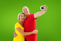 Composite image of happy mature couple taking a selfie together Stock Photography