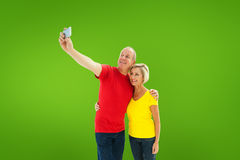 Composite image of happy mature couple taking a selfie together. Happy mature couple taking a selfie together against green vignette Royalty Free Stock Photo