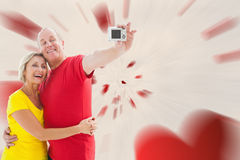 Composite image of happy mature couple taking a selfie together. Happy mature couple taking a selfie together against love heart pattern Stock Photos