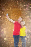 Composite image of happy mature couple taking a selfie together. Happy mature couple taking a selfie together against white snow and stars on black Royalty Free Stock Photos