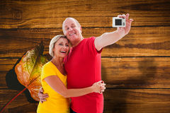Composite image of happy mature couple taking a selfie together. Happy mature couple taking a selfie together against wooden table with autumn leaves Stock Photos