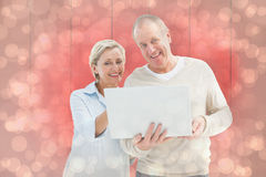 Composite image of happy mature couple using laptop Stock Photos
